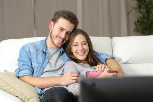 50532995 - happy couple watching a movie on tv sitting on a couch at home